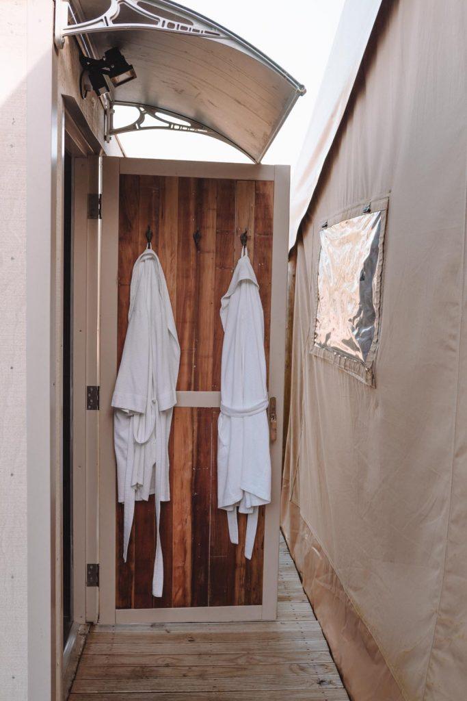 Luxury Glamping badezimmer mit duschgel, shampoo, conditioner und handtüchern und bademäntel