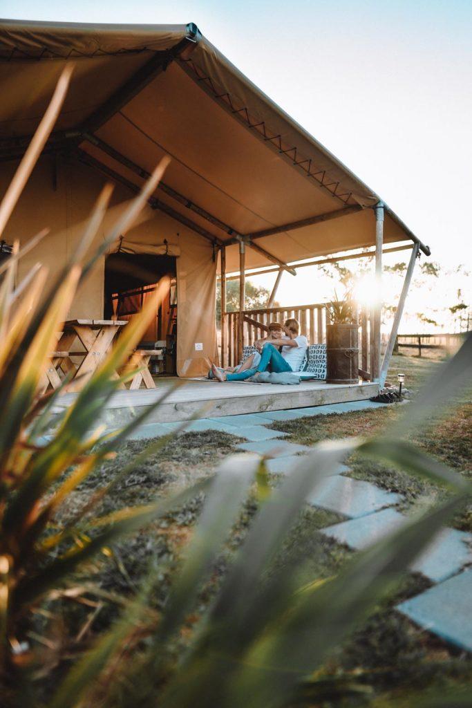 Luxury Glamping Paar beim Entspannen auf der Terrasse mit Sonnenuntergang vorm Safari Zelt